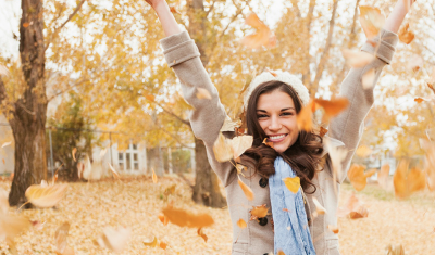 Woman Throwing Fall Leaves in Air