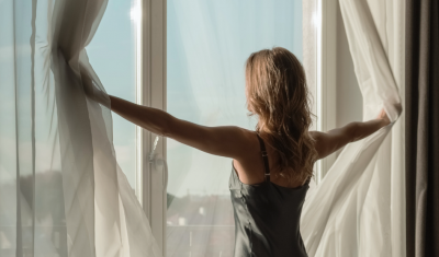 Woman Opening Curtains In Front of Window